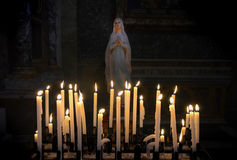 Virgin Mary with candlelights. Virgin Mary with candle lights in front in a catholic church royalty free stock photos