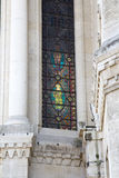 Virgin Mary holding a flowers in her hand on a stained glass window Stock Photos
