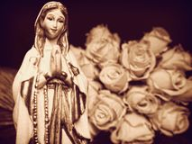 Virgin Mary mother of God praying rosary Christian statue statuette figurine and white roses Royalty Free Stock Photography