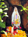 Virgin mary statue. With garlands in cave royalty free stock images
