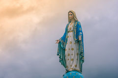 Virgin Mary Statue At Catholic Church With Sunlight In Cloudy Day Background.