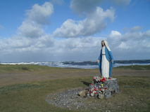 Virgin Mary statue on the beach. Virgin Mary statue with floral offerings on the beach in La Paloma, a seaside resort located in the Department of Rocha, Uruguay Stock Photos