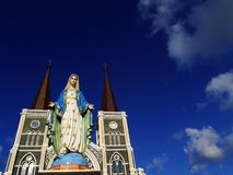 Virgin Mary Statue com fundo da igreja e do céu azul foto de stock royalty free