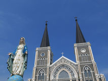 Virgin mary statue in front of church. On blue sky background Royalty Free Stock Photography