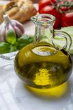 Virgin natural olive oil is glass bottle, served with traditional Mediterranean food. Fresh tomatoes, olive bread, basil, fennel royalty free stock image