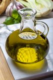 Virgin natural olive oil is glass bottle, served with traditional Mediterranean food. Fresh tomatoes, olive bread, basil, fennel royalty free stock photo