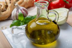 Virgin natural olive oil is glass bottle, served with traditional Mediterranean food. Fresh tomatoes, olive bread, basil, fennel stock photo