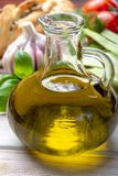 Virgin natural olive oil is glass bottle, served with traditional Mediterranean food. Fresh tomatoes, olive bread, basil, fennel stock image