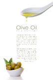 Virgin olive oil dripping from a spoon and olive seeds Stock Photo