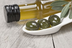 Virgin olive oil and green olives Stock Images