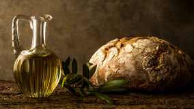 Virgin olive oil in vintage oil jar and rustic bread Stock Photos