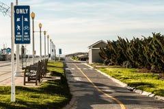 Virginia Beach Boardwalk med cykelbanan och bänkar Arkivfoto