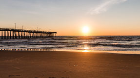 Virginia Beach Fishing Pier with Sun at Horizon. Virginia Beach, Virginia boardwalk fishing pier with the sun at the horizon Royalty Free Stock Photography