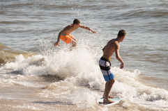 Virginia Beach Skim Boarders. An image of people skimboarding at the beach at the Virginia Beach Boardwalk stock images