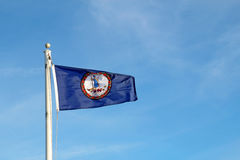 Virginia state flag against a blue sky. Flag of the Commonwealth of Virginia flying from a while pole against a bright blue sky and cirrus clouds background stock photography