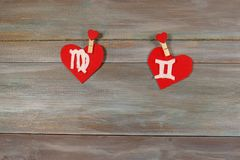 Virgo and twins. signs of the zodiac and heart. wooden backgroun stock photography