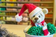 virka nallebjörnen i en röd julhatt handgjord amigurumi Arkivfoton