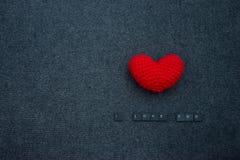 Virka röd hjärta på svart bakgrund och inskriften som jag älskar dig Arkivfoton