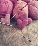 Virka rosa hjärtor och garn på träbakgrund. Royaltyfria Foton