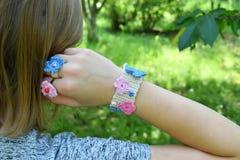 Virkade dina egna smycken Rosa färger och blåttarmband och hårlock på ung flicka Moment 3 - färdigt gods DIY-projekt affär isoler Royaltyfri Bild