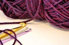 Virkningkrokar och purpurfärgat garn Royaltyfri Bild