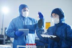 Virologen die bloedonderzoeken doen stock afbeelding