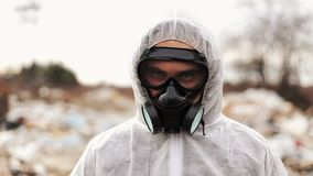 Virologist man in protective costume and respirator gas mask looking in camera on in landfill site pollution, ecological. Disaster stock footage