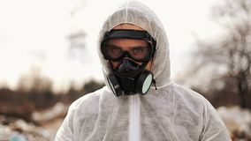 Virologist man in protective costume and respirator gas mask looking in camera on in landfill site pollution, ecological. Disaster stock video