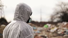 Virologist man in protective costume and respirator gas mask walking near landfill site pollution, ecological disaster.  stock footage