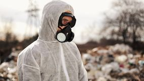 Virologist man in protective costume and respirator gas mask walking near landfill site pollution, ecological disaster.  stock video footage