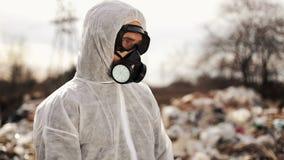 Virologistman i skyddande dräkt- och respiratorgasmask som går nära förorening för nedgrävning av soporplats, ekologisk katastrof lager videofilmer