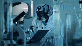 Virologists in hazmats work with microscopes to research a coronavirus sample.