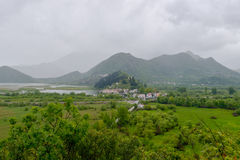 Virpazar villiage, Montenegro. Virpazar villiage on the shore of the Skadar Lake   surrounded by mountains and trees at rainy evening in Montenegro Stock Images