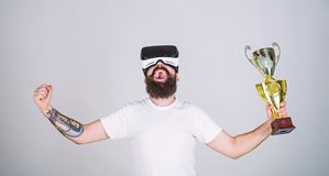 Virtual achievement concept. Guy with VR glasses won championship, hold in hand golden goblet. Man with beard in VR. Glasses is winner, grey background. Hipster royalty free stock photo