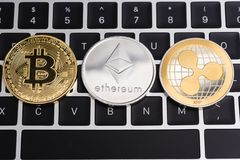 Virtual Bitcoin, ripple XRP and Ethereum coins currency finance. Money on computer laptop keyboard royalty free stock photo
