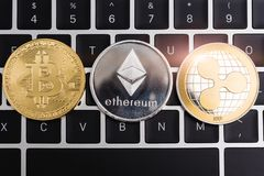 Virtual Bitcoin, ripple XRP and Ethereum coins currency finance money. On computer laptop keyboard royalty free stock image
