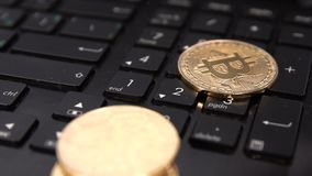 Bitcoin coin on a keyboard slow motion falling.