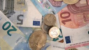 Bitcoin coins EU Euro banknotes and cents slow motion falling.