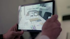 Virtual drawing of house on tablet. Stock. Businessman holding tablet with virtual reality project at home in boardroom