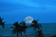 A virtual full moon makes a spectacular entrance to the twilight sky over the tropical ocean below stock image