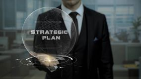Virtual hologram Strategic Plan held by male auditor in the office. Animated cyber Earth turns on the hand of inspector and words appear stock video