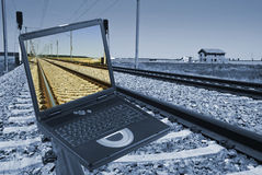 Virtual journey to the unknown. The picture shows a laptop on the railways in high contrast and the screen of laptop display the continuity of the rail in color stock photo