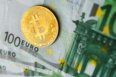 Virtual money golden bitcoin on hundred euro bills background. Exchange bitcoin cash for euro concept stock photography