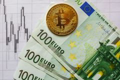Virtual money golden bitcoin on hundred euro bills and on paper forex chart index background. Exchange bitcoin cash for euro stock photo