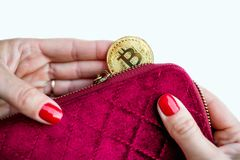 Virtual money golden bitcoin on pink women fabric purse. fingers with red nails on a coin isolated on white background royalty free stock photos