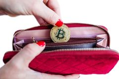 Virtual money golden bitcoin on pink women fabric purse. fingers with red nails on a coin isolated on white background stock photography
