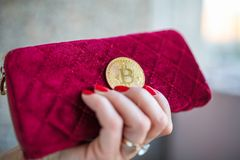 Virtual money golden bitcoin on pink women fabric purse. fingers with red nails on a coin stock image