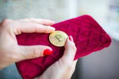 Virtual money golden bitcoin on pink women fabric purse. fingers with red nails on a coin royalty free stock photos