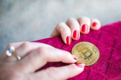 Virtual money golden bitcoin on pink women fabric purse. fingers with red nails on a coin royalty free stock images