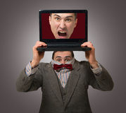 Virtual personality concept. Timid man holds the laptop showing his aggressive virtual personality Stock Photos